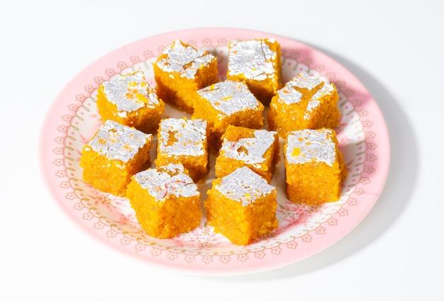 Alimento dolce indiano mung dal chakki o moong dal barfi su bianco