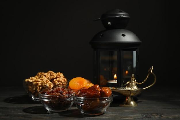 Alimento e decorazione di ramadan kareem sulla tavola di legno contro fondo scuro