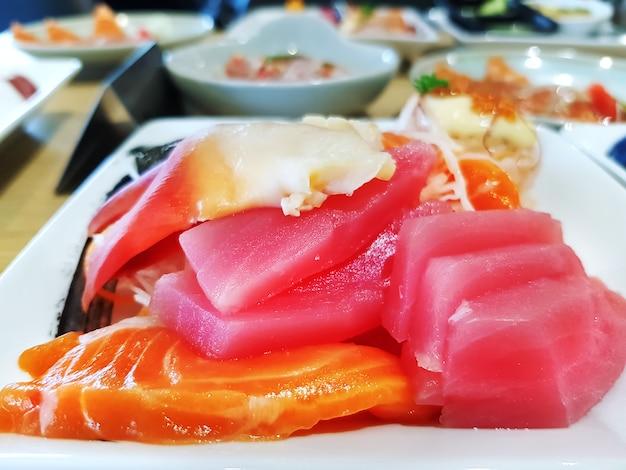 Alimento giapponese del sashimi di tonno e del salmone sul piatto bianco
