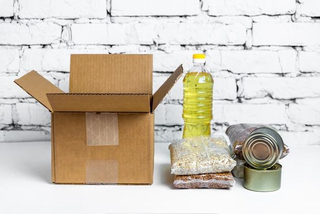 Alimento in scatola di donazione del cartone su un fondo bianco. scorte anticrisi di beni essenziali per il periodo di isolamento in quarantena. consegna del cibo, coronavirus. la carenza di cibo.