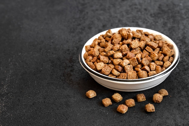 Alimento per animali domestici asciutto in una ciotola ceramica bianca su fondo nero con lo spazio della copia