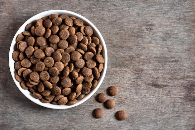 Alimento per animali domestici asciutto in una ciotola ceramica bianca su superficie di legno