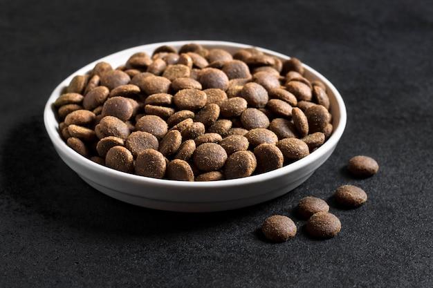 Alimento per animali domestici asciutto in una ciotola di ceramica bianca su superficie nera