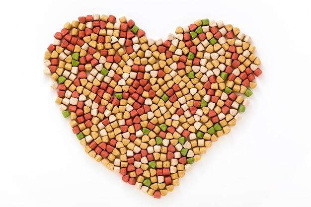 Alimento per animali domestici asciutto sotto forma di una forma del cuore isolata su fondo bianco