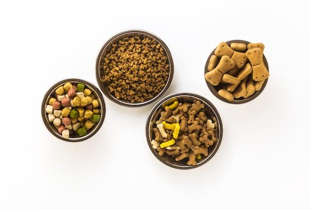 Alimento per animali domestici in ciotole e giocattoli isolati su fondo bianco