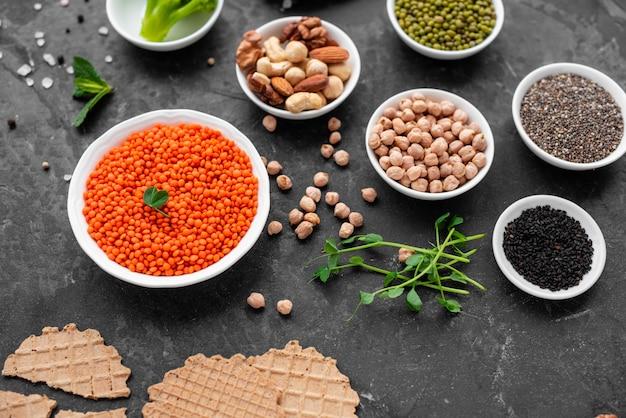 Alimento sano del vegano su una priorità bassa concreta con lo spazio della copia. noci, fagioli, verdure e semi