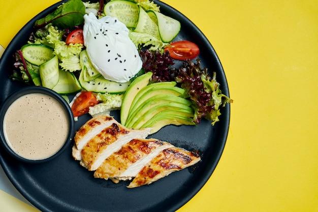 Alimento sano e dietetico - filetto di pollo al forno con lattuga e uovo affogato in un piatto ceramico nero su superficie colorata vista superiore