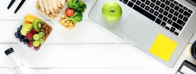Alimento sano in scatola del pasto messo sul tavolo di lavoro con il computer portatile