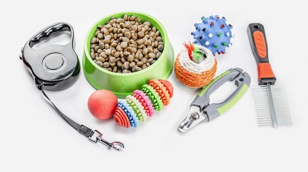 Alimento secco con accessori per animali domestici su bianco isolato