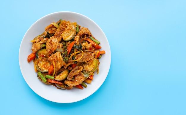 Alimento tailandese, carne di maiale in padella piccante con le erbe