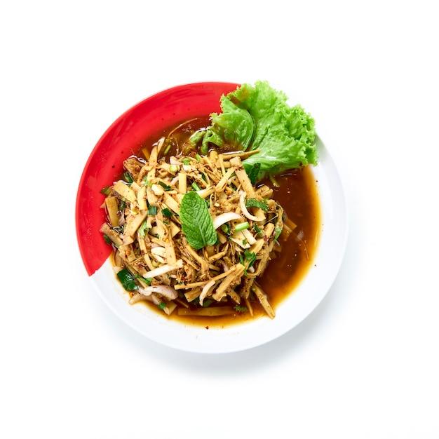 Alimento tailandese insalata piccante del germoglio di bambù servito con la verdura fresca su bianco