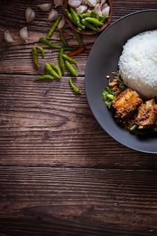 Alimento tailandese, riso condito con basilico fritto in padella e osso di maiale.