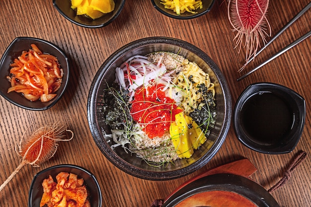 Alimento tradizionale coreano di disposizione piana con il kimchi su fondo di legno. spaghetti coreani con cipolle, salsa rossa e sesamo, carne di pollo. cucina asiatica tradizionale. pranzo. cibo salutare