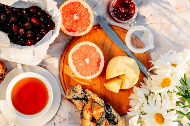 All'aperto parcheggiare il cibo. frutta, croissant, marmellata, tè e fiori sulla tovaglia al sole.