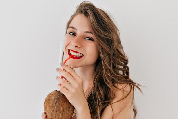 All'interno felice donna elegante con labbra rosse e denti bianchi e una pelle sana con i capelli ricci beve cocco e posa