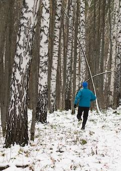 All'uomo piace correre nella foresta invernale.