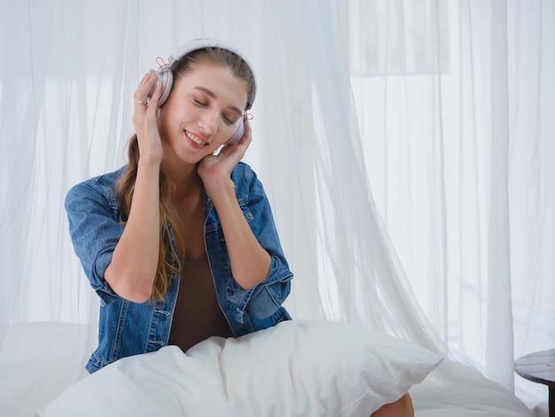 Alla donna piace ascoltare la musica a casa, la ragazza si rilassa ascoltando la musica nel letto