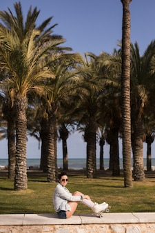 Alla moda attraente giovane donna sorridente seduto vicino alla spiaggia