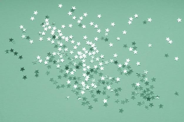 Alla moda neo menta di coriandoli di stelle d'argento su verde