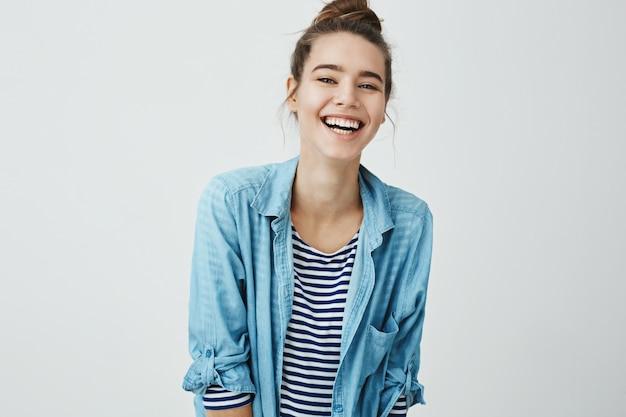 Alla ragazza piacciono le battute divertenti. studente intelligente di bell'aspetto con acconciatura da panino che trema dalla risata, sorride positivamente ed è di ottimo umore stando in piedi. orologio da donna spettacolo esilarante