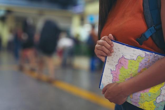 Alle donne piace viaggiare sulla mappa per la stazione ferroviaria.