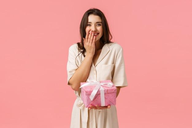 Allegra adorabile giovane ragazza bruna in abito alla moda, sorridente e risatina toccata, ricevendo un regalo fantastico, regalo di compleanno o scatola da giorno per donna, in piedi parete rosa deliziata