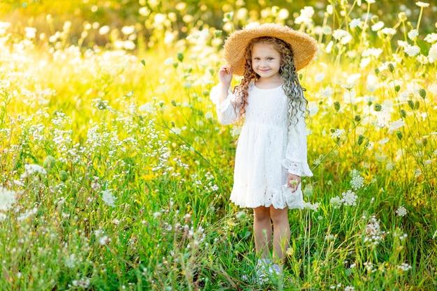 Allegra bella ragazza in un cappello di paglia in estate in un campo giallo con fiori