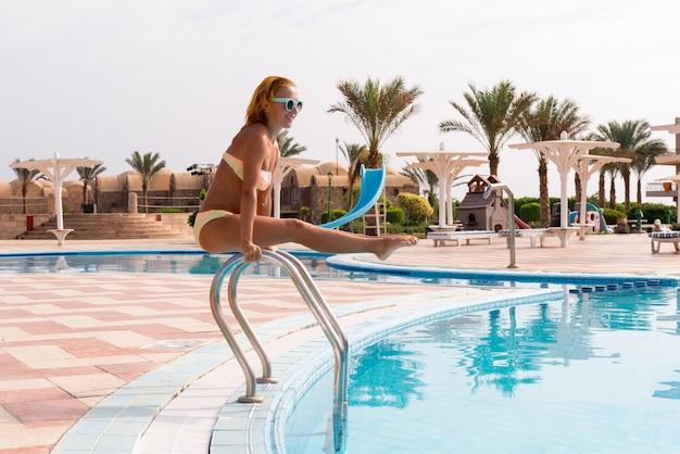 Allegra donna sottile sulle rotaie della piscina