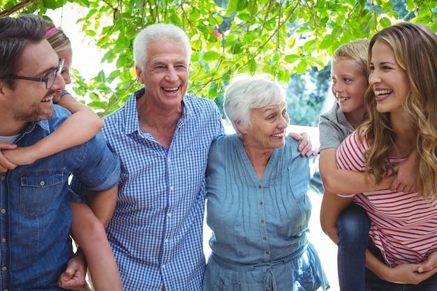 Allegra famiglia di diverse generazioni con genitori che danno sulle spalle