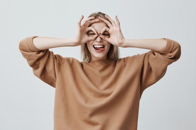 Allegra femmina eccitata con lunghi capelli lisci biondi che mostra gesti ok con entrambe le mani, fingendo di indossare gli occhiali e sorridendo ampiamente, godendosi la sua spensierata vita felice