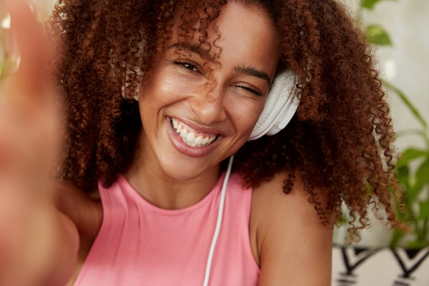 Allegra gioiosa donna afroamericana posa per selfie, ha un ampio sorriso, ascolta la traccia preferita in cuffia, si gode il tempo libero, si siede in un'accogliente caffetteria. persone e concetto di intrattenimento