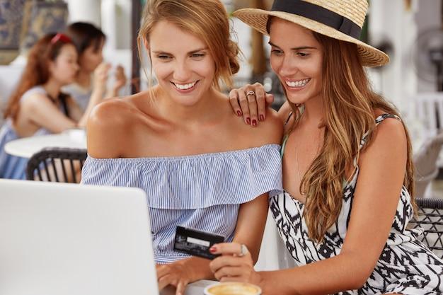 Allegre giovani donne blogger lavorano al computer portatile nella caffetteria, usano la carta di plastica per pagare online, riposano nella caffetteria con terrazza. le coppie lesbiche fanno shopping nel negozio di internet.