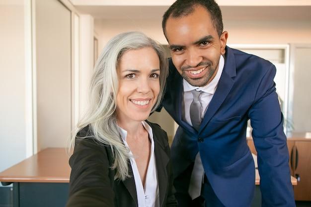 Allegri partner professionali in posa per la foto, sorridendo e guardando la fotocamera. datore di lavoro di successo afroamericano dell'ufficio e donna di affari caucasica che prendono selfie. lavoro di squadra e concetto di affari