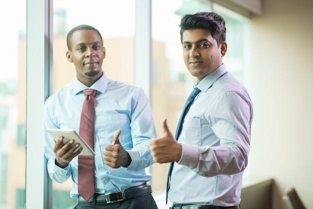Allegri uomini d'affari multietnici che mostrano il pollice in su