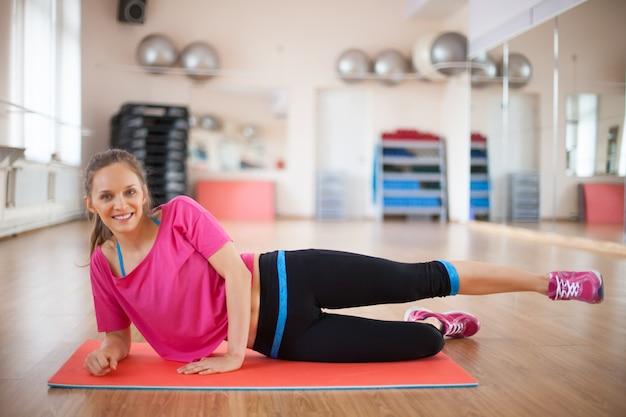 Allegro allenatore di forma fisica mostrando esercizio fisico
