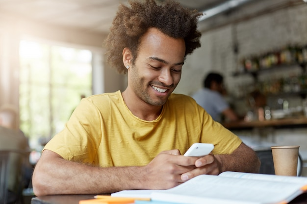 Allegro bel giovane studente afroamericano maschio in maglietta gialla che passa in rassegna internet sullo smart phone, avendo resto al negozio di caffè