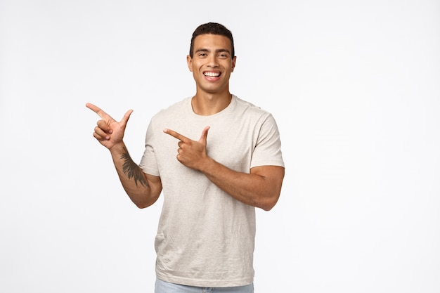 Allegro bell'uomo muscoloso con tatuaggio sul braccio, abbronzatura, indossa una maglietta bianca