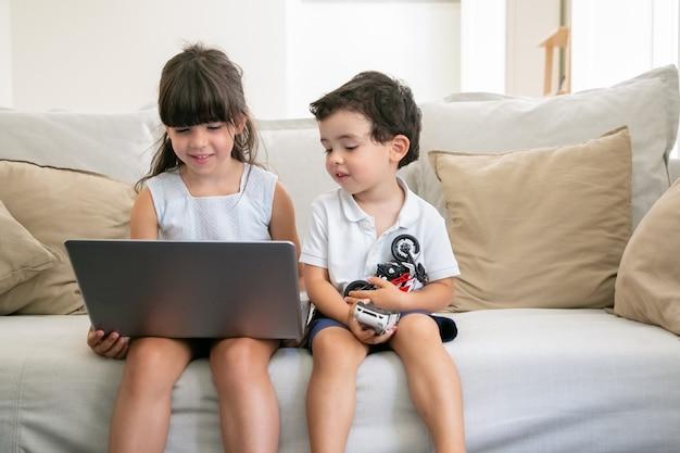 Allegro fratellino e sorella seduti sul divano a casa, utilizzando laptop, guardando video, film di cartoni animati o film divertenti.