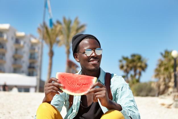 Allegro giovane maschio afroamericano vestito con abiti alla moda che si divertono all'aperto in riva al mare, godendo dell'anguria succosa matura e del bel tempo soleggiato, sorridendo ampiamente, ammirando il bellissimo paesaggio marino
