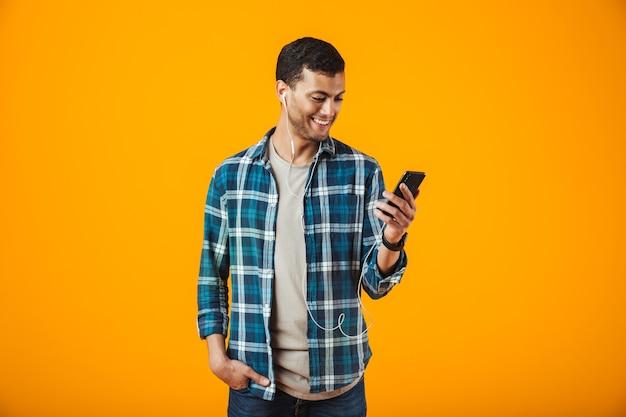 Allegro giovane uomo che indossa la camicia a quadri in piedi isolato su sfondo arancione, ascoltando la musica con gli auricolari, tenendo il telefono cellulare