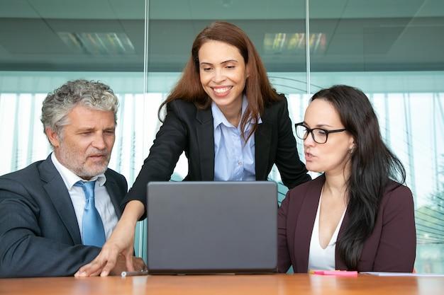 Allegro manager fiducioso condividere idee con i colleghi, mostrando la presentazione sul computer.