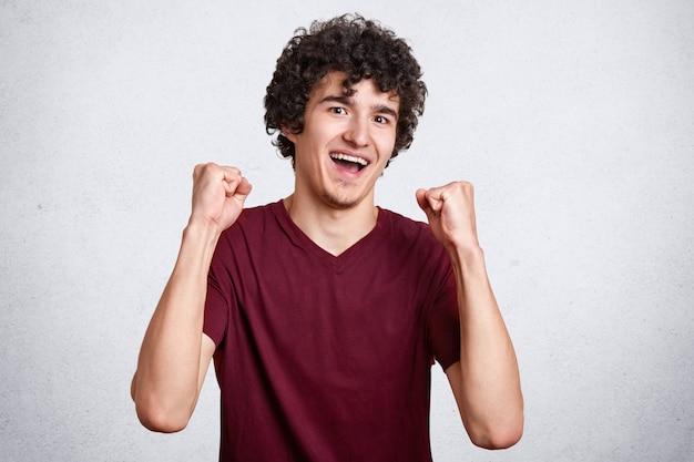 Allegro maschio europeo attraente che è eccitato e felice di raggiungere la vittoria, esprime positività, stringe i pugni, screma evviva