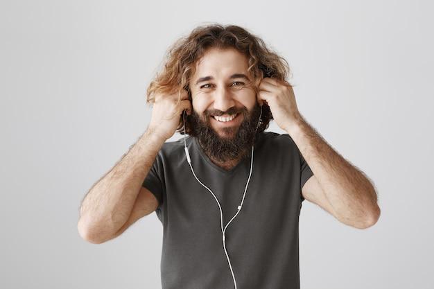 Allegro ragazzo barbuto indossa gli auricolari e sorride felice, ascoltando musica