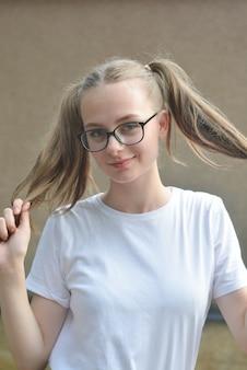 Allegro ragazzo carino positivo, ragazza di età adolescente, essendo di ottimo umore e mostrando il suo sorriso e le code di capelli lunghi.
