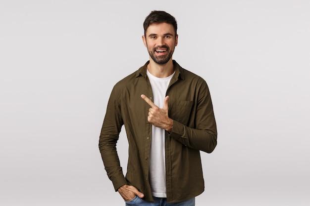Allegro, simpatico ragazzo barbuto bello in abito moderno, che punta a sinistra, presenta la persona agli amici o raccomandare posto negozio, raccolta del prodotto, sorridendo volentieri, prenotazione
