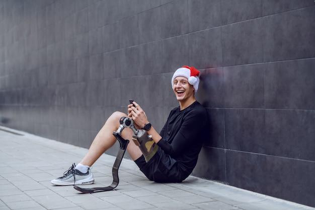 Allegro sportivo caucasico con gamba artificiale e con cappello da babbo natale sulla testa seduto a terra, appoggiato al muro e inviando auguri di natale sul suo smart phone.