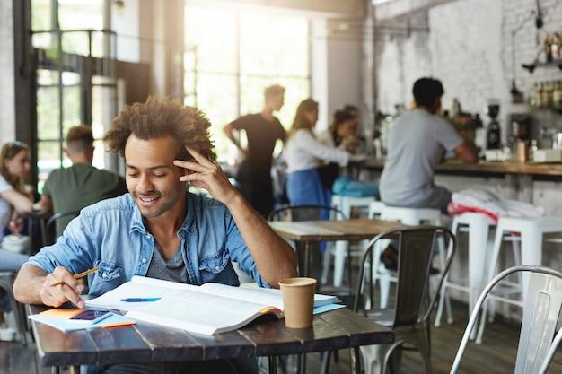 Allegro studente nero con elegante taglio di capelli afro che sorride ampiamente durante la lettura del messaggio sul cellulare, navigando in internet durante la pausa pranzo mentre si fanno i compiti presso la caffetteria