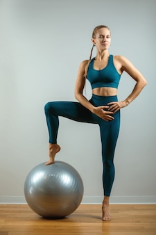 Allenamento a casa. istruttore di fitness con fitball su uno spazio grigio. allenamenti con vari inventari spot. copia spazio, fitness baren.