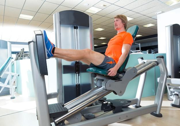 Allenamento biondo della macchina della stampa della gamba messo palestra