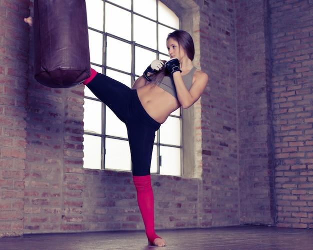 Allenamento combattente. donna che perfora il sacco pesante di pugilato